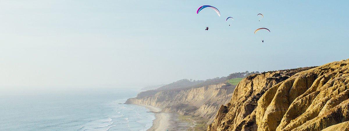 Parapentes volant en uns penyasegats davant el mar