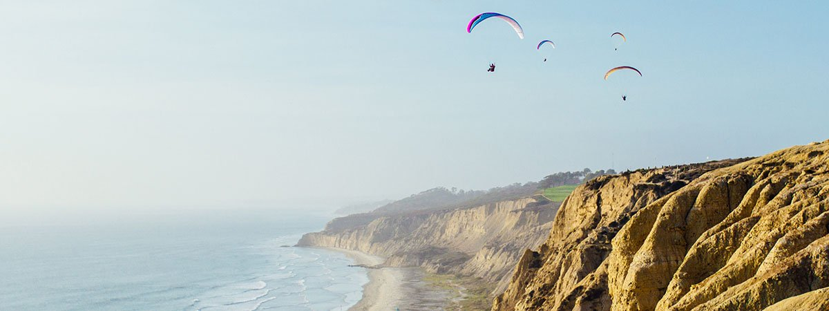 paragliders on cliffs in front of the sea